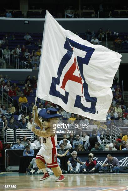 The Arizona Wildcats mascot runs across the court with a flag during the game against the UCLA Bruins in the Pac 10 tournament on March 13 2003 at...