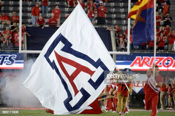 The Arizona Wildcats mascot runs on the field with an Arizona Wildcats flag for the game between the Washington State Cougars and Arizona Wildcats at...