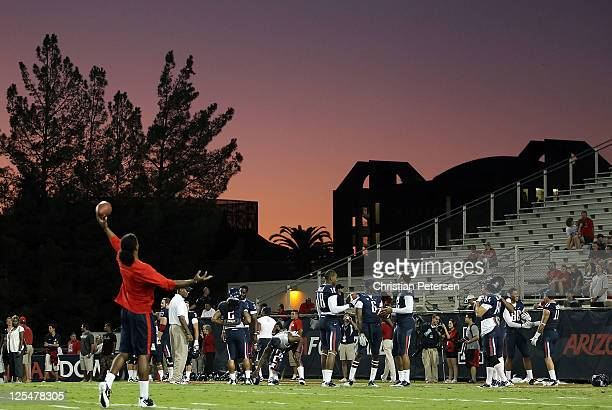 The Arizona Wildcats warm up on the field as the sun sets before the college football game against the Stanford Cardinal at Arizona Stadium on...