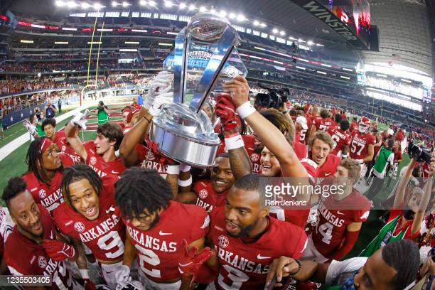 The Arkansas Razorbacks celebrate with the Southwest Classic championship trophy following the teams 20-10 win over Texas A&M Aggies at AT&T Stadium...