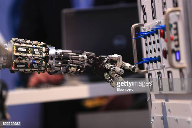 The arm of an AILA mobile dualarm robot system demonstrates the flicking of switches at the CeBIT 2017 tech fair in Hannover Germany on Monday March...