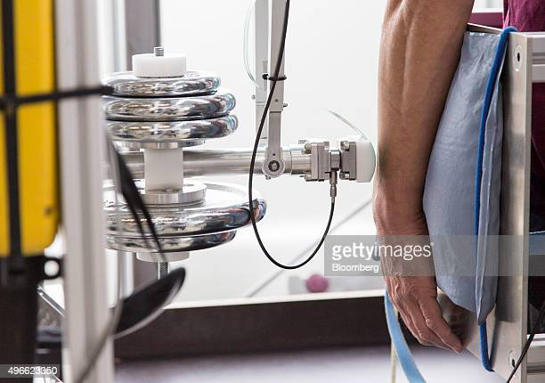 The arm of volunteer Stephan Bernstein is strapped to a cushion beside a mechanical pendulum pain threshold testing machine at the robot collision...