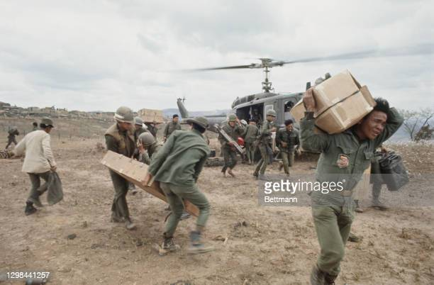 The Army of the Republic of Vietnam carrying supplies from the Bell UH-1 helicopter, colloquially known as 'Huey Slick', at Fire Support Base Delta...