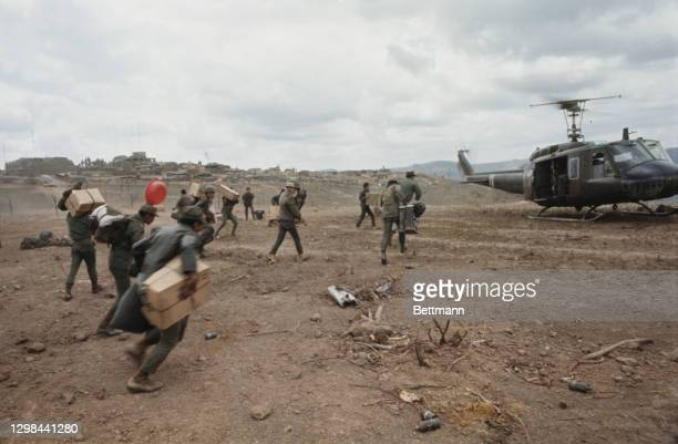 The Army of the Republic of Vietnam rushing towards the Bell UH-1 helicopter, colloquially known as 'Huey Slick', at Fire Support Base Delta One in...