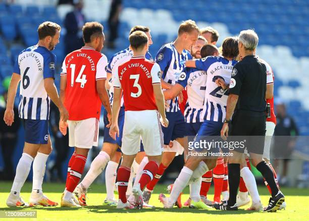 The Arsenal and Brighton and Hove Albion players clash as referee Martin Atkinson attempts to break them up during the Premier League match between...