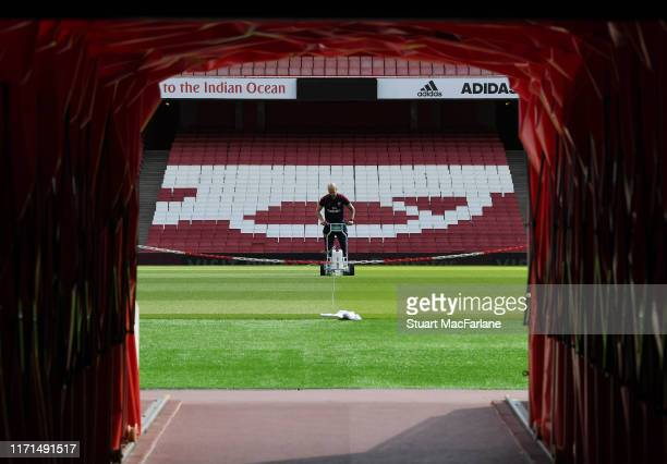 The Arsenal groundsman marks out the pitch before the Premier League match between Arsenal FC and Tottenham Hotspur at Emirates Stadium on September...