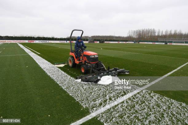 The Arsenal groundstaff clear the pitch of snow before the match between Arsenal U23 and Chelsea U23 at London Colney on March 17 2018 in St Albans...