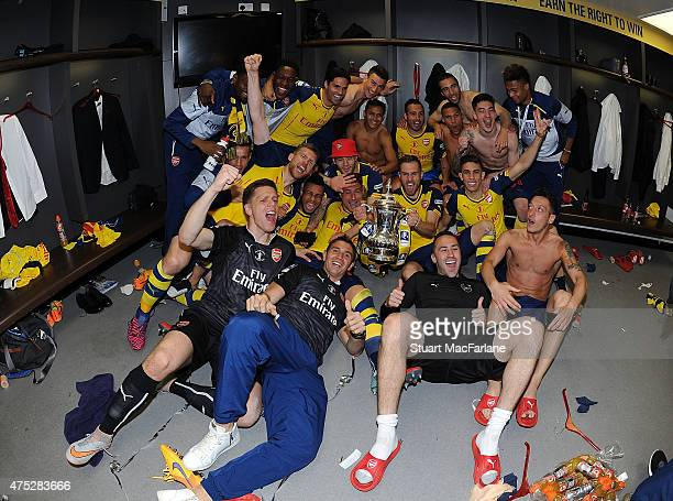 The Arsenal squad celebrate in the dressing room after winning the Cup after the FA Cup Final between Aston Villa and Arsenal at Wembley Stadium on...