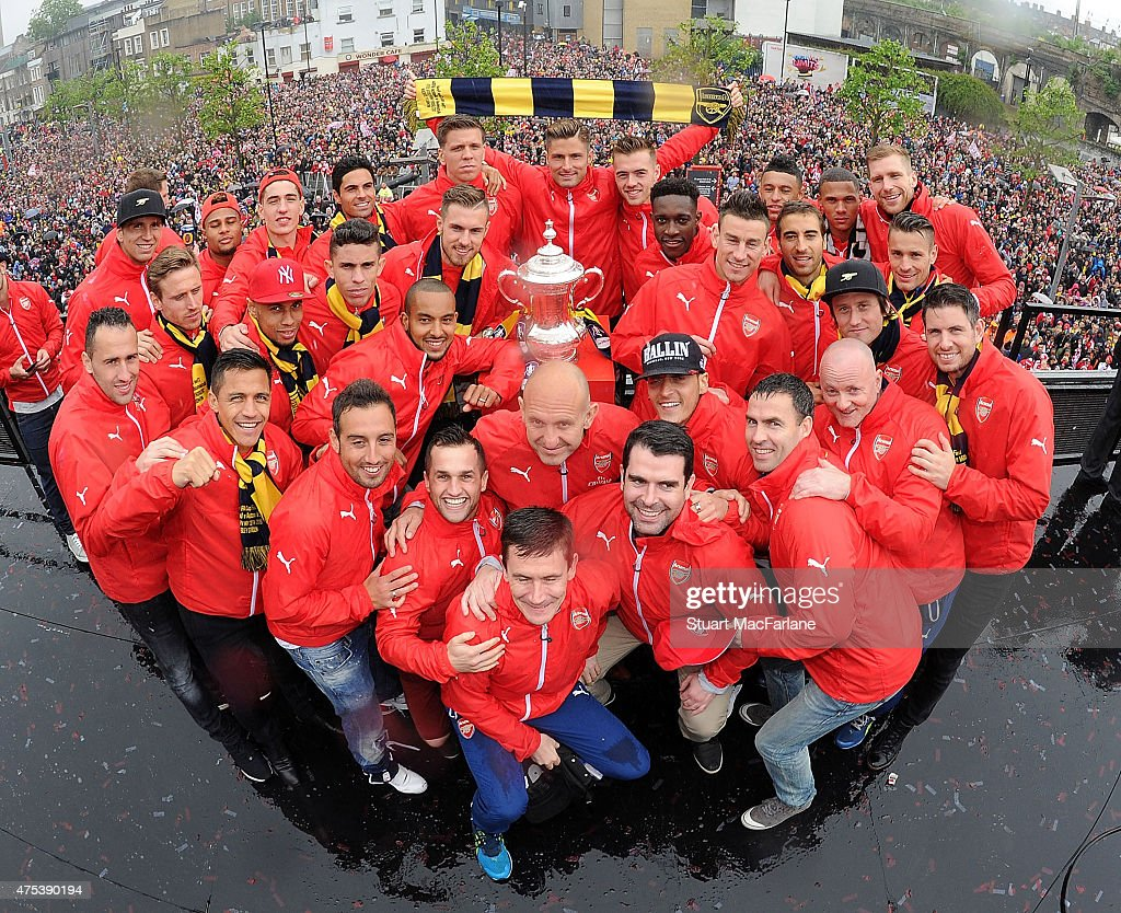 The Arsenal squad pose with the cup during the Arsenal FA Cup Victory Parade in Islington on May 31, 2015 in London, England.