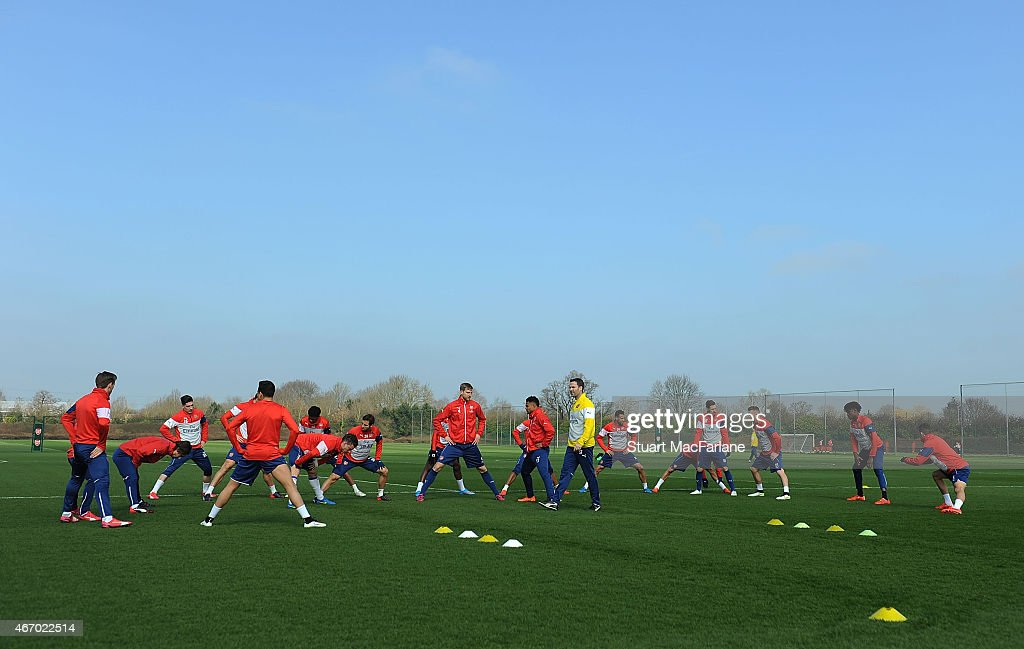 The Arsenal squad warm up before a training session at London Colney on March 20, 2015 in St Albans, England.