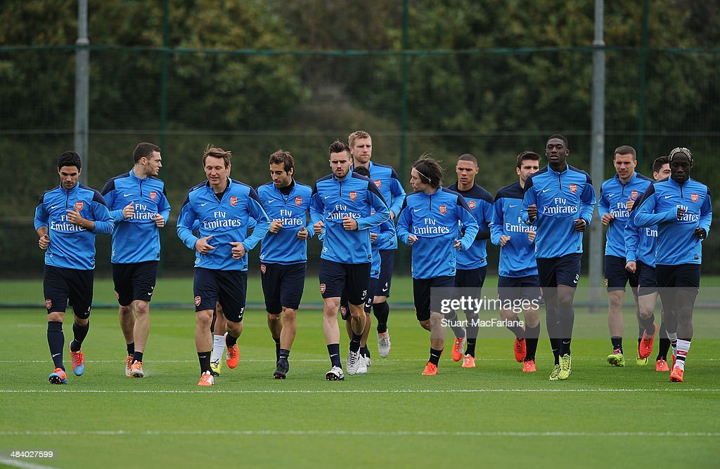 ST. ALBANS, ENGLAND - The Arsenal squad warm up before a training session at London Colney on April 11, 2014 in St Albans, England.
