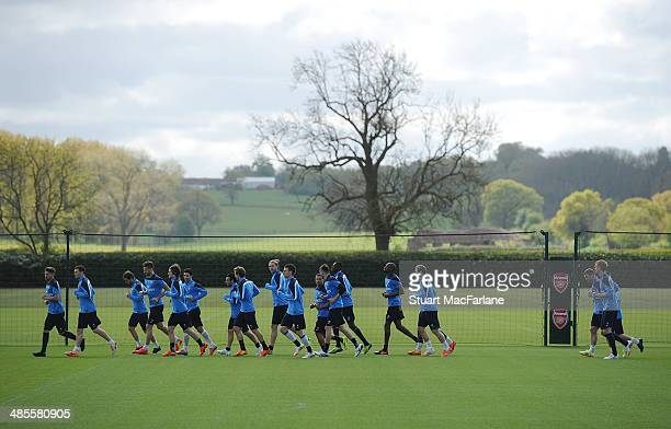 The Arsenal squad warm up before a training session at London Colney on April 19, 2014 in St Albans, England.