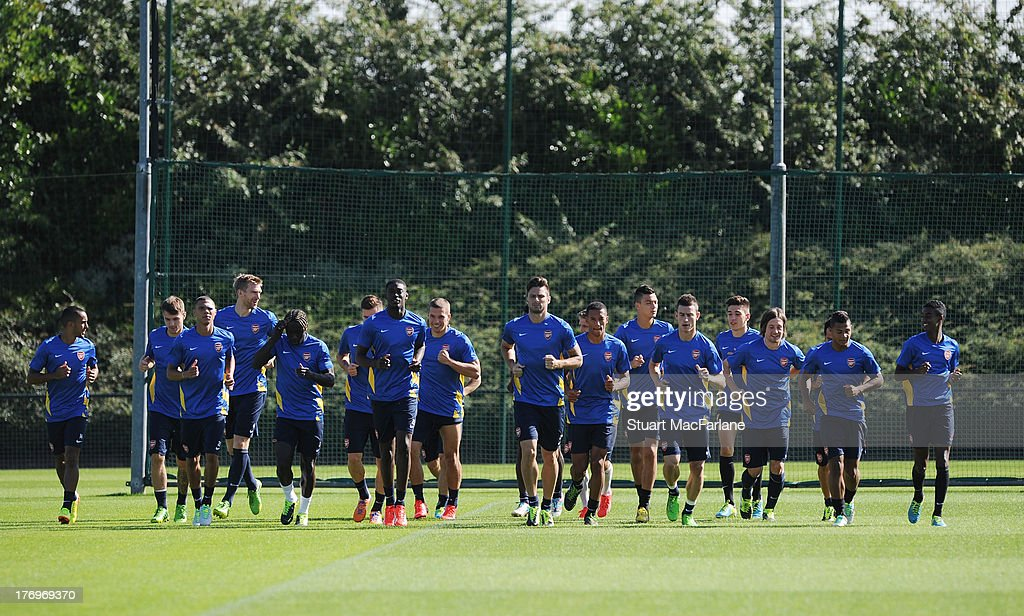 The Arsenal squad warn up before a training session ahead of their UEFA Champions League Play Off first leg match against Fenerbache at London Colney on August 20, 2013 in St Albans, England.