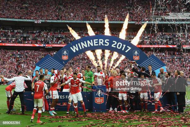 The Arsenal team celebrate with the FA Cup after The Emirates FA Cup Final between Arsenal and Chelsea at Wembley Stadium on May 27 2017 in London...