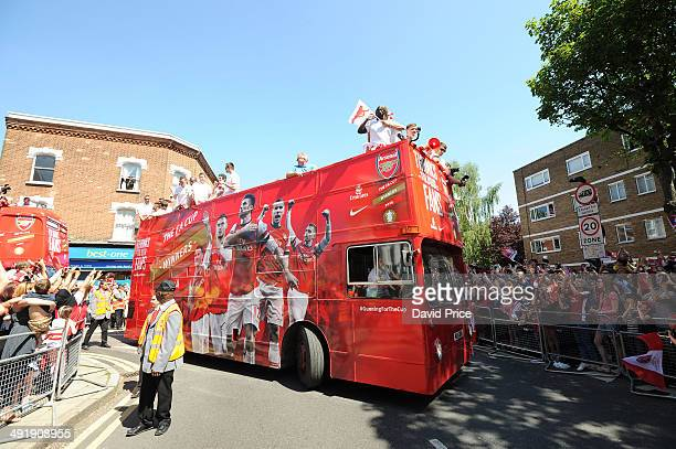 The Arsenal team parade with the FA Cup trophy through the streets of Islington on May 18 2014 in London England
