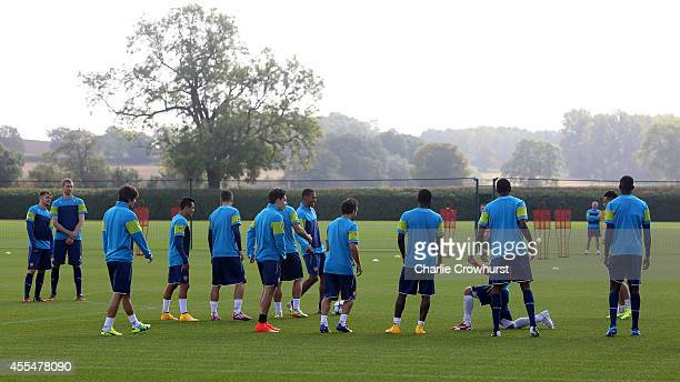 The Arsenal team warm up during a Arsenal Training Session ahead of their Champions League fixture against Borussia Dortmund on September 15 2014 in...