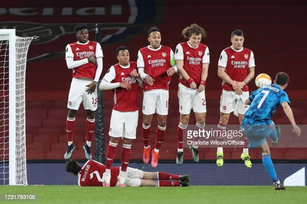 The Arsenal wall of Thomas Partey, Gabriel, Pierre-Emerick Aubameyang, David Luiz and Granit Xhaka jump to block a free-kick from Costs Fortounis of...