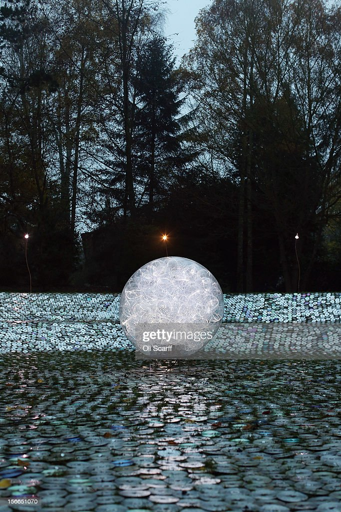 The art installation by Bruce Munro entitled 'Blue Moon on a Platter', made up of thousands of used CDs, forms part of the Christmas decorations at Waddesdon Manor on November 16, 2012 in Aylesbury, England. The piece, which is located on the banks of Waddesdon's amphitheatre, measures 28 meters across and in the centre a 1.5m 'Moon' of optic fibres glows with blue light. The East Wing and Bachelor's Wing of Waddesdon Manor have been elaborately decorated for Christmas in the theme of English traditions and literature. The light-artist Bruce Munro has also created two installations in the grounds of the manor. The Christmas decorations at Waddesdon Manor are open to the general public until January 1, 2013.