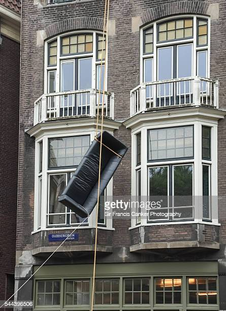 The art of moving house in Amsterdam with a couch hanging in middle of street