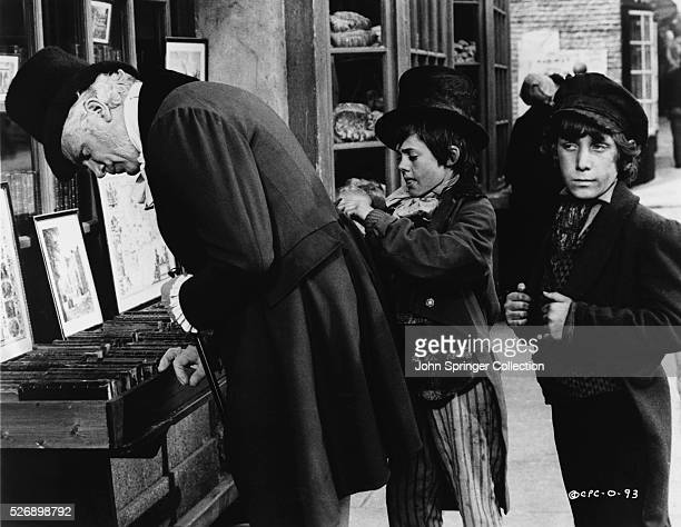 The Artful Dodger skillfully picks the pocket of a gentleman shopper as another boy keeps lookout in the 1968 musical Oliver!.