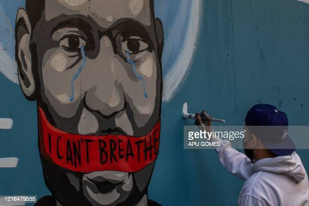 TOPSHOT The artist Celos paints a mural in Downtown Los Angeles on May 30 2020 in protest against the death of George Floyd an unarmed black man who...