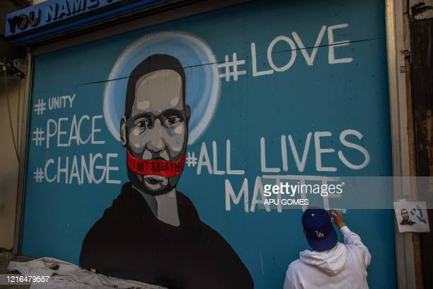 The artist Celos paints a mural in Downtown Los Angeles on May 30 2020 in protest against the death of George Floyd an unarmed black man who died...
