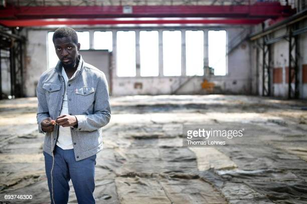 The artist Ibrahim Mahama of Ghana works on jute bags for his next artwork at Henschel Hall on June 8 2017 in Kassel Germany The documenta 14 is the...