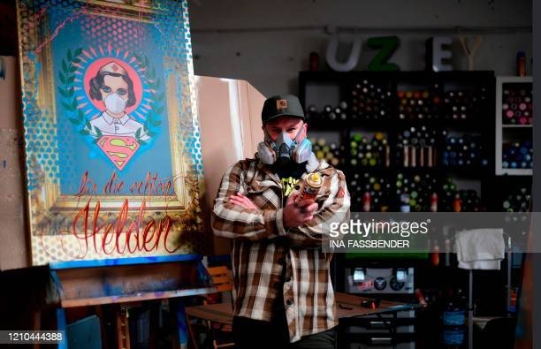 The artist Kai 'Uzey' Wohlgemuth poses next to a painting with a nurse as Superwoman and the lettering for the real heroes in his artist studio in...
