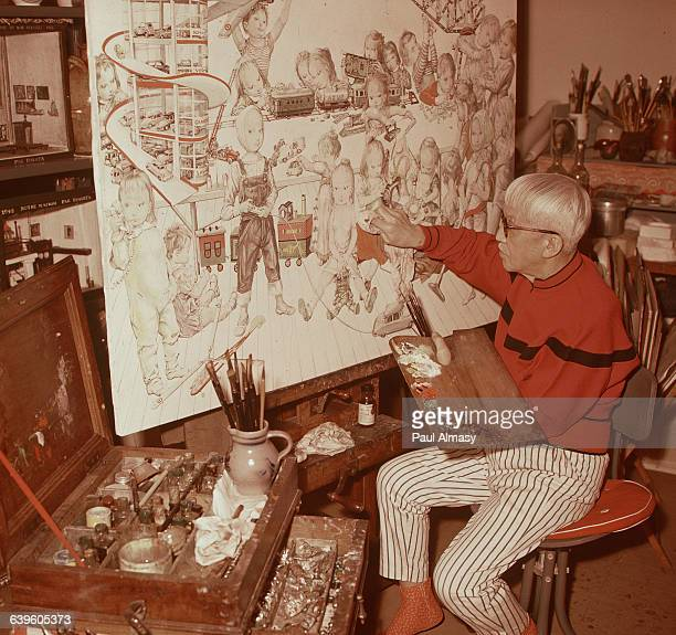 The artist Tsougharu Foujita at work on a painting of children playing | Location Foujita's studio in France
