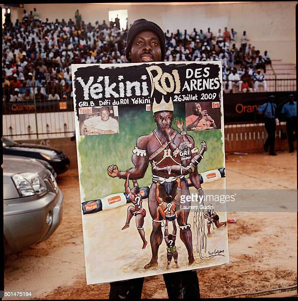 The artist Vieux Coly shows of his painting of wrestler Yekini as a display of support at the Demba Diop Stadium in Dakar Senegal