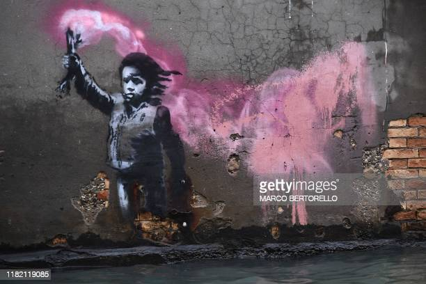 The artwork by street artist Banksy, that portrays a migrant child wearing a lifejacket and holding a neon pink flare, is pictured after an...