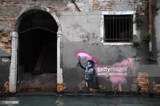 TOPSHOT The artwork by street artist Banksy that portrays a migrant child wearing a lifejacket and holding a neon pink flare is pictured after an...