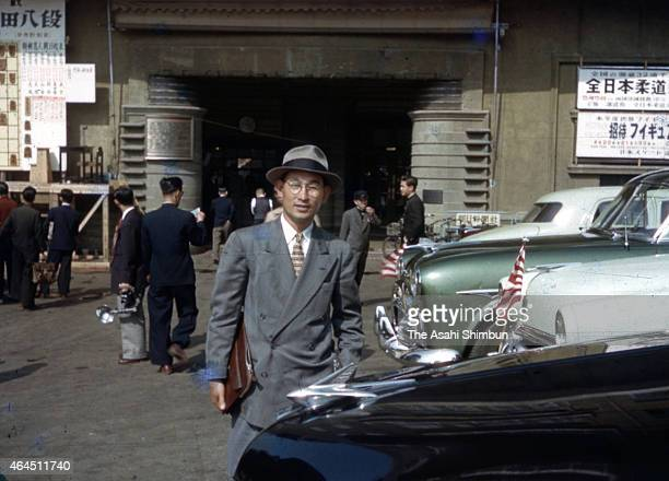 The Asahi Shimbun photographer Tasuo Tomishige pose for photographs in front of the Tokyo headquarters on April 29 1952 in Tokyo Japan Japan restored...