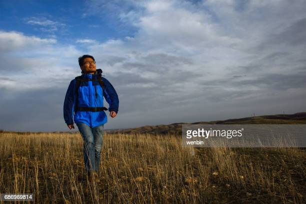 The asian traveller hiked in the field with his bag on his back
