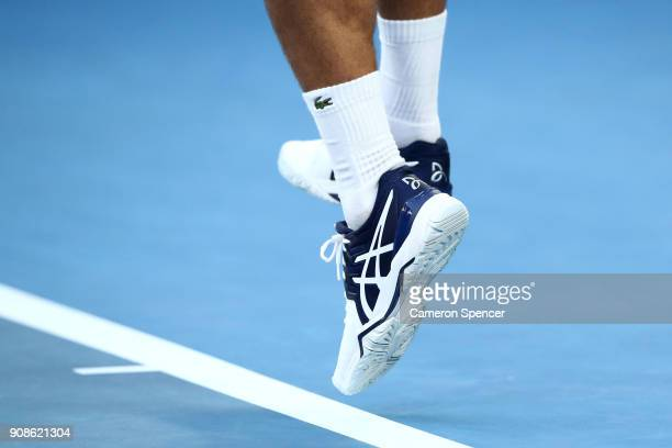 The Asics shoes of Novak Djokovic of Serbia are seen in his fourth round  match against