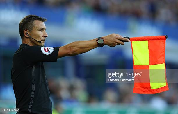The assisstant referee holds up the offside flag during the Premier League match between Everton and Middlesbrough at Goodison Park on September 17...