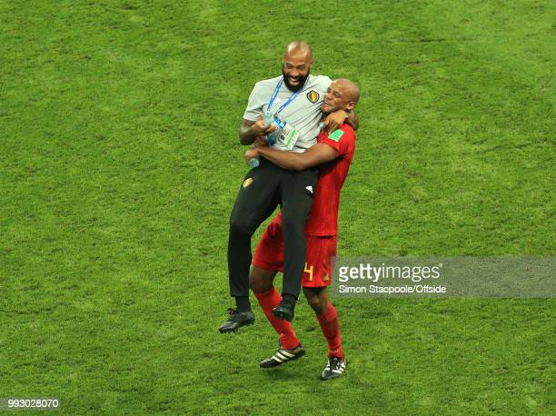 The assistant coach of Belgium Thierry Henry is lifted by Vincent Kompany of Belgium after the 2018 FIFA World Cup Russia Quarter Final match between...