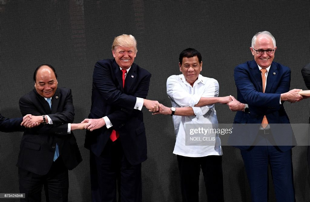 TOPSHOT - (L-R) The Association of Southeast Asian Nations (ASEAN) members Vietnam's Prime Minister Nguyen Xuan Phuc, US President Donald Trump, Philippine President Rodrigo Duterte, Australia Prime Minister Malcolm Turnbull, link hands during the Opening ceremony of the 31st ASEAN Summit in Cultural Center of the Philippines (CCP) in Manila on November 13, 2017. World leaders are in the Philippines' capital for two days of summits. /