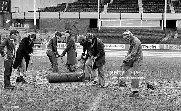 The Aston Villa groundsman enlists some extra help from the Villa apprentices who are put to work on the muddy pitch at Villa Park in Birmingham 24th...