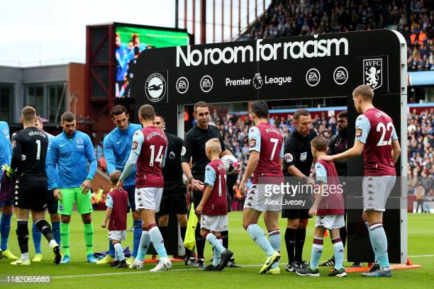The Aston Villa players walk out onto the pitch with branding for the 'No room for racism' campaign branding in the background prior to the Premier...