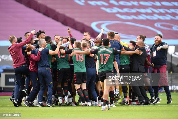 The Aston Villa team and staff celebrate after finding out they are staying in the Premier League after the Premier League match between West Ham...