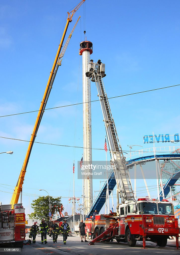 The Astrotower is disassembled in Coney Island on July 4, 2013 in the Brooklyn borough of New York City. Officials decided to close Luna Park and sections of the boardwalk while workers take down the amusement tower which was seen precariously swaying two days ago.