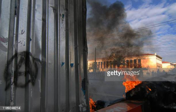 The Athens University is pictured behind burning tires during clashes 02 February 2008 Police fired tear gas when rival farright and anarchist...