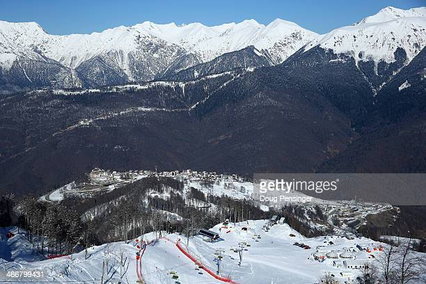The athlete's Olympic Village sits on a plateau below the snow capped peaks as the women's alpine ski course desends the mountain in the foreground...