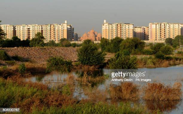 The Athlete's Village and Akshardham Temple are seen from across the Yamuna river in New Delhi India