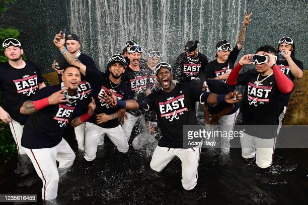 The Atlanta Braves celebrate in the center field waterfall after winning the NL Eastern Division against the Philadelphia Phillies at Truist Park on...