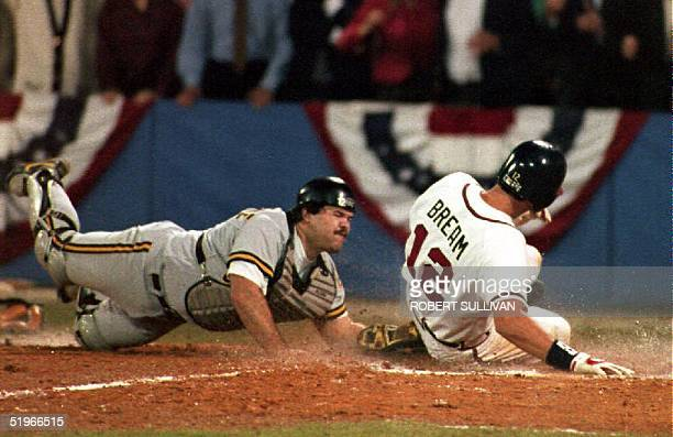 The Atlanta Braves Sid Bream slides across the plate to win the National League Championship Series as the Pittsburgh Pirates catcher Mike LaValliere...
