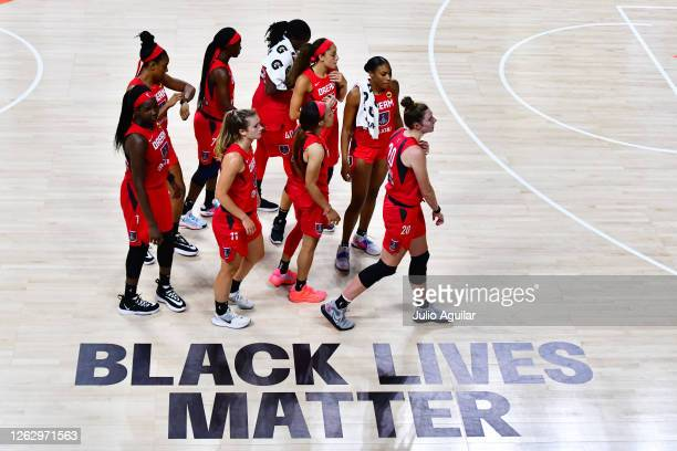 The Atlanta Dream walk by the Black Lives Matter graphic on the court following a 100-70 loss to the Las Vegas Aces at Feld Entertainment Center on...