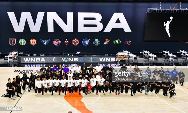 The Atlanta Dream, Washington Mystics, Minnesota Lynx, and the Los Angeles Sparks kneel on the court after the teams collectively decided to postpone...