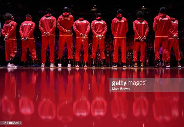 The Atlanta Hawks line up for the national anthem prior to preseason action against the Miami Heat at FTX Arena on October 04, 2021 in Miami,...